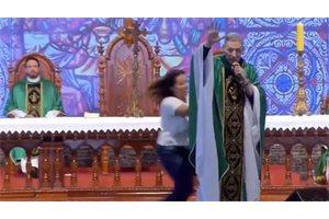 Una mujer empuja y tira del altar al famoso padre Marcelo Rossi durante una misa en Brasil