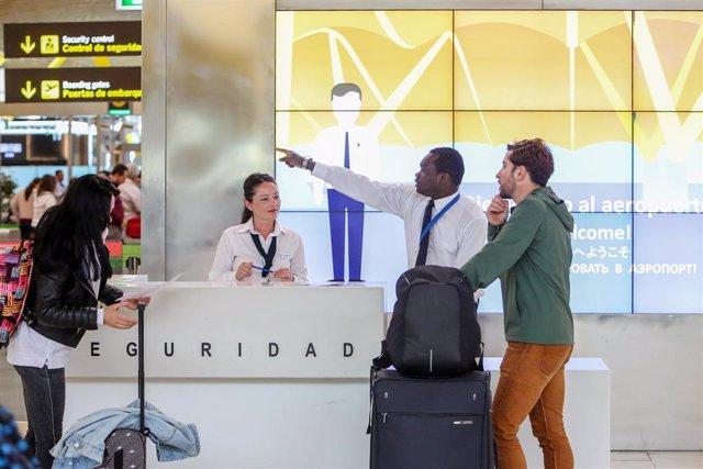 Un trabajador del stand de Seguridad del Aeropuerto Adolfo Suárez Madrid- Barajas, indica a un viajero el acceso al control de seguirdad de la terminal.