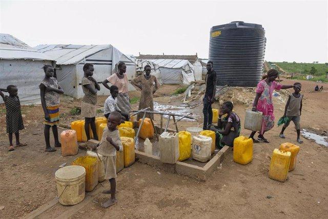 Mujeres y niños en un pozo de agua en un campamento de desplazados de la ONU en la capital de Sudán del Sur, Yuba.