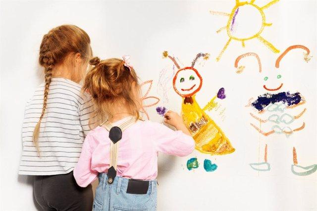 Dos niñas pintando en la pared de una escuela infantil.