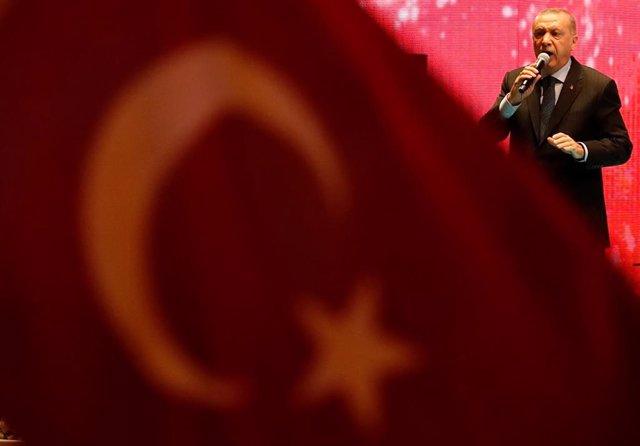 Recep Tayyip Erdogan junto a la bandera de Turquía