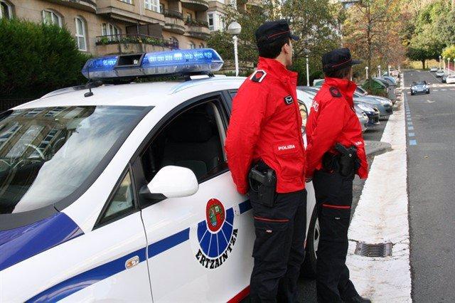 Agentes de la Ertzaintza junto con su coche