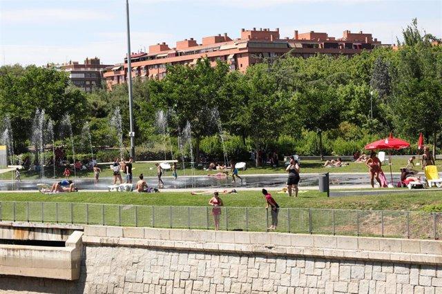 Varias personas, se refrescan de las altas temperaturas en las inmediaciones de los chorros de Madrid Río un día antes de que, según la Agencia Estatal de Meteorología (AEMET), llegue a la península Ibérica y a las Islas Baleares la primera ola de calor d