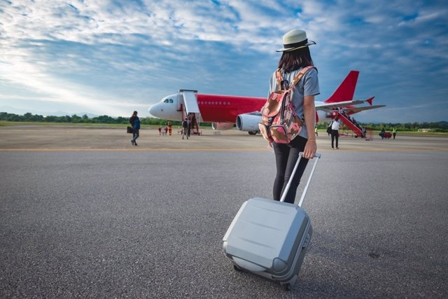 Girl traveler with luggage going to plane