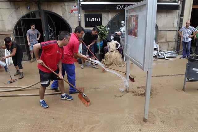 Varios vecinos limpian la calle tras las graves inundaciones en Tafalla.