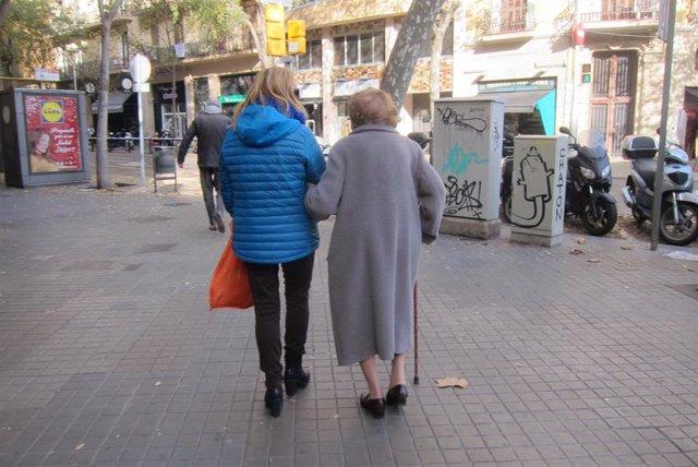 Imagen de archivo de una cuidadora con una anciana dependiente.