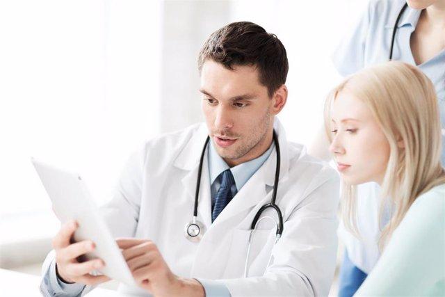 Consulta médico. Médico muestra una tablet a una paciente. Asistencia sanitaria.