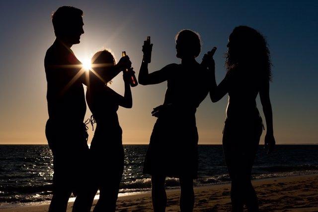 Jóvenes bebiendo en una playa.