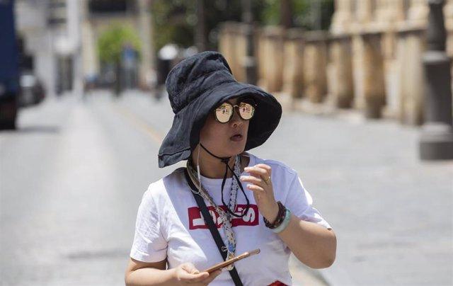 Imágenes de recurso de subida de temperaturas en la segunda semana de Julio 2019. Turista asiática se protege del sol en la calle Santo Tomás.