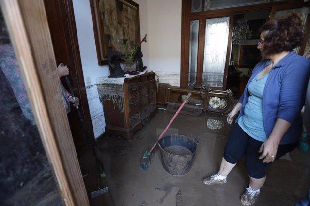 Una mujer achica agua en el interior de su casa en Sant Llorenç (Mallorca) tras las inundaciones por las fuertes lluvias