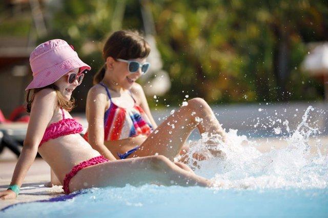 Niñas chapoteando en una piscina en verano.