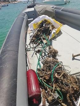Una embarcación durante las tareas de limpieza de fondos marinos en Ses Figueres