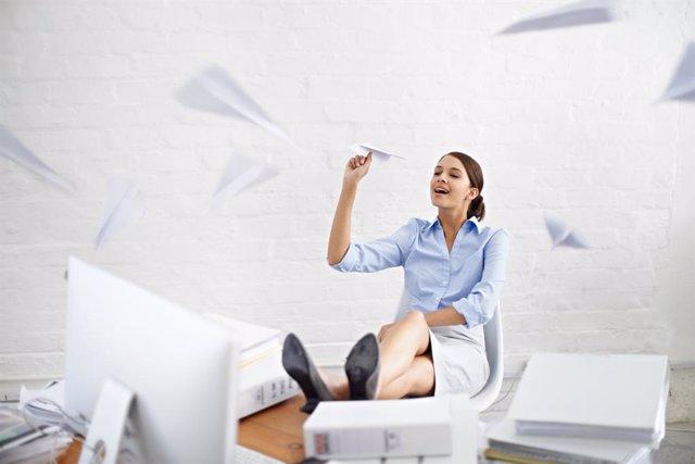 Procastinar, mujer dejando pasar el tiempo en la oficina haciendo aviones de papel.