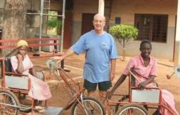 El misionero británico Trevor Robinson junto a dos de los triciclos que ha fabricado para personas con discapacidad en Ghana