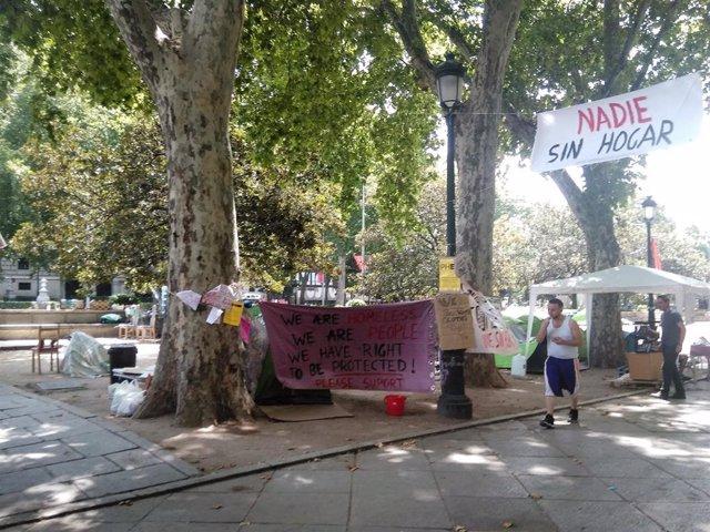 Imagen de carteles reivindicativos en el Paseo del Prado de la acampada de personas sin techo.