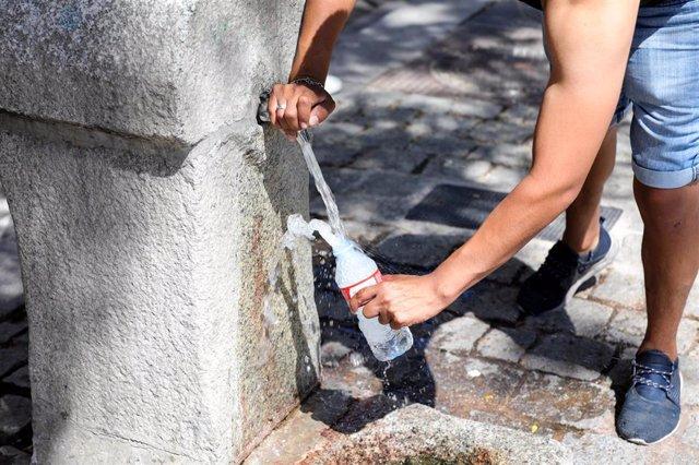 Un hombre rellena una botella de agua durante la ola de calor de esta semana
