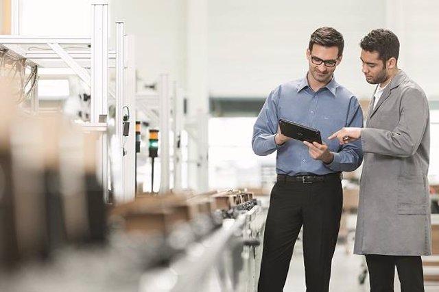 Trabajadores en una fábrica usando tecnología