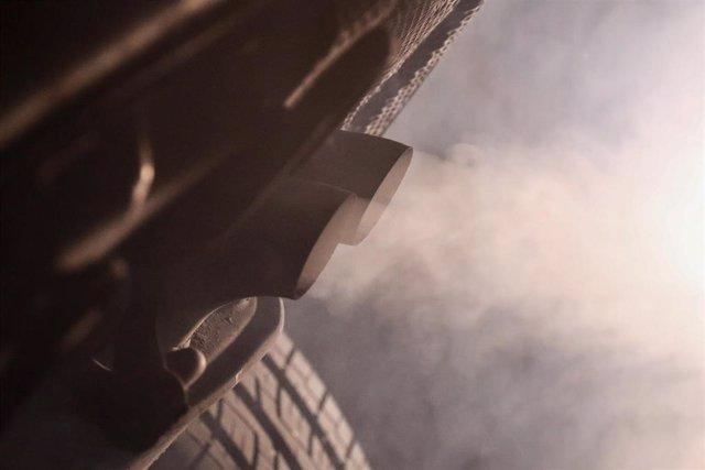 Tubo de escape de un coche emitiendo polución.