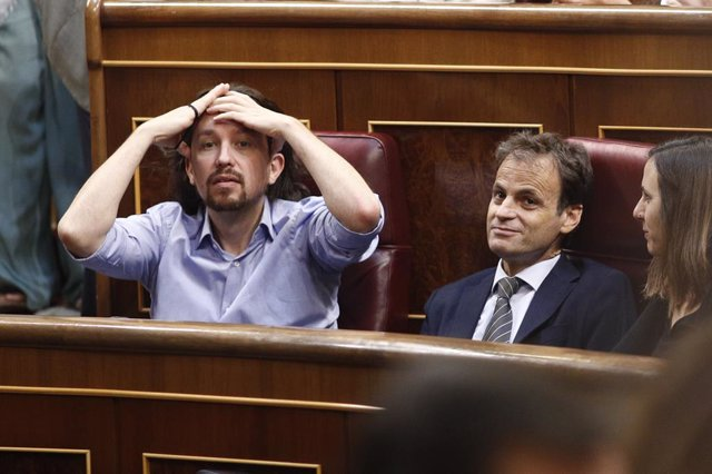 El secretari general d'Unides Podem, Pablo Iglesias (portant-se les mans al capdavant); el portaveu d'ECP al Congrés, Jaume Asens; i la portaveu adjunta de Podem al Congrés, Ione Belarra, asseguts en els seus escons durant la segona sessió de