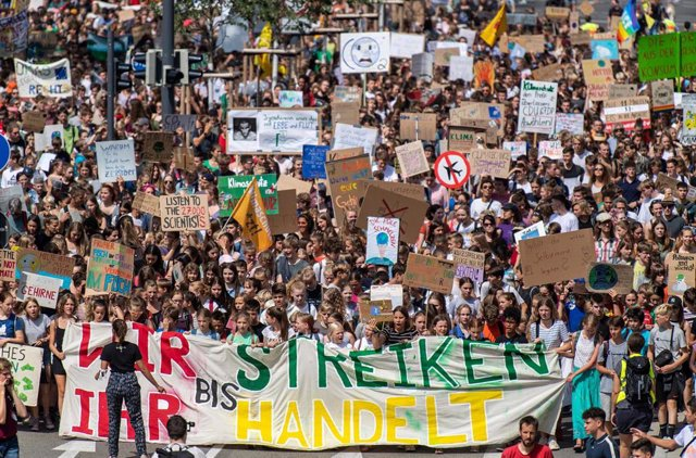 19 July 2019, Baden-Wuerttemberg, Freiburg: Participants hold placards during the Fridays for Future - climate strikes for the implementation of the Paris World Climate Agreement. Photo: Patrick Seeger/dpa