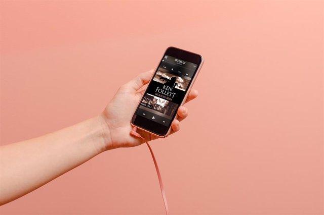Imagen de un usuario sosteniendo un smartphone con el que escucha un audiolibro