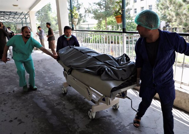 Emergency workers transport the dead body of a victim to the hospital after a blast in Kabul, Afghanistan