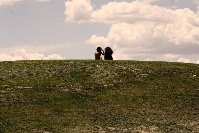 Una pareja de jóvenes disfruta de un soleado día sentados en el césped del parque de las 'Siete Tetas' de Vallecas.