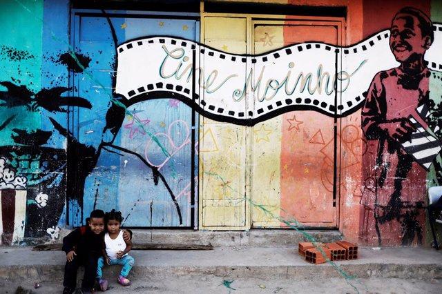 Dos niños en la entrada de un cine en la favela de Moinho en Sao Paulo