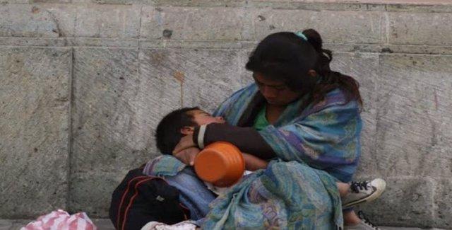 Mendiga con niño en brazos