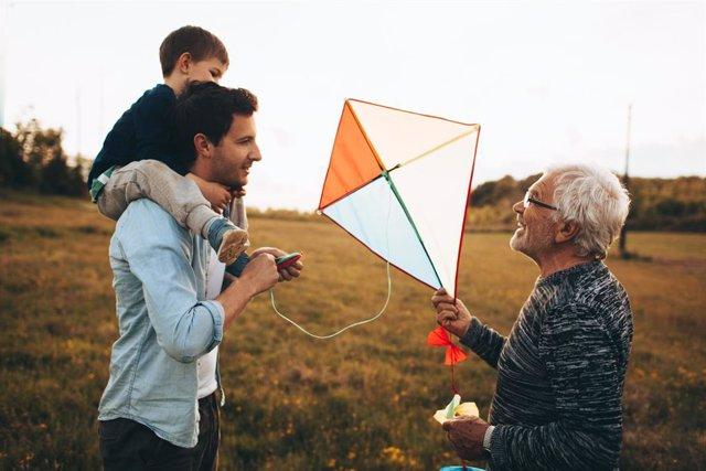 Tres generaciones, abuelo, padre y nieto, juegan a la cometa.