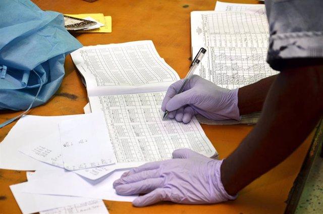 Una persona con guantes de látex rellena unos datos en un cuaderno