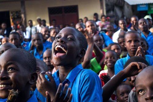 Niños africanos sonriendo en una actividad para promover el liderazgo de la empresa en la lucha contra la pobreza