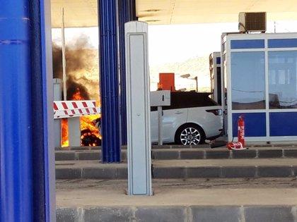 Bomberos trabajan en la extinción de un vehículo incendiado en el peaje de la A-7, a su paso por Vera (Almería)