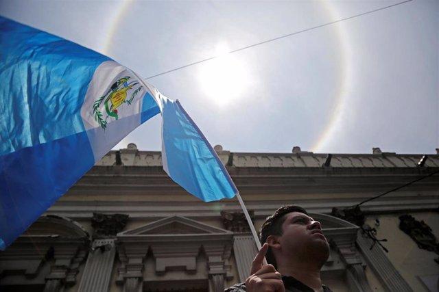 Un hombre ondea una bandera de Guatemala.