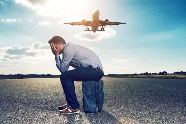 Pasajero con jet lag sentado sobre su maleta en el aeropuerto sobrevolado por un avión.