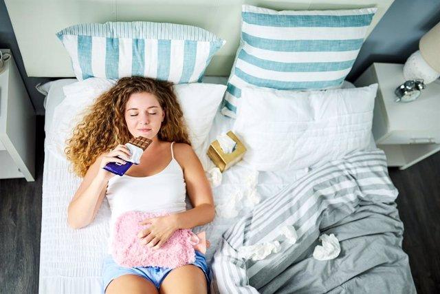 Síndrome premenstrual, comiendo chocolate en la cama con bolsa de agua caliente.