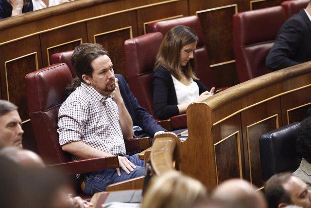 El secretari general de Podem, Pablo Iglesias, escolta amb gest seriós el discurs del president del Govern en funcions previ a la  segona votació per a la investidura del candidat socialista a la Presidència del Govern. Iglesias va confirmar prev