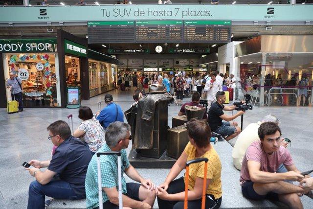 Passatgers en l'estació de tren Puerta d'Atocha de Madrid esperen amb les seves maletes al costat d'un panell d'informació de l'horari de trens durant la primera de les quatre jornades d'aturs parcials de Renfe als quals el sindicat CGT ha convocat als t