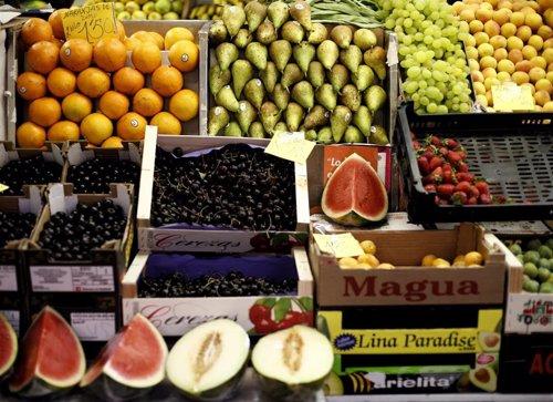 Naranjas, peras, limones, uvas, sandías, melones, fresas y cerezas en un mercado.
