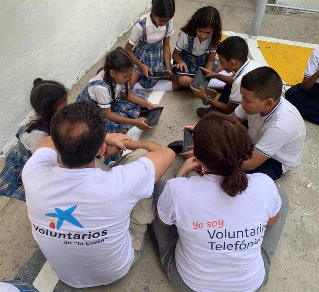 Voluntarios de Telefónica y La Caixa con un grupo de niños participantes en ProFuturo.