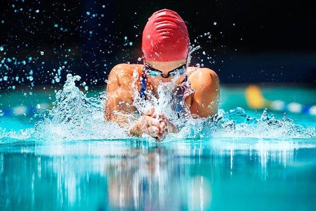 Mujer haciendo natación en una pisina, nadando.