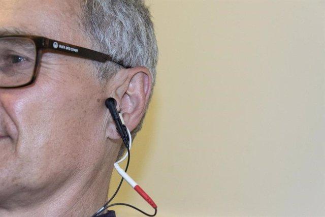 Un dispositivo tVNS se adhiere al oído y suavemente proporciona estimulación eléctrica, que reequilibra el sistema nervioso autónomo.