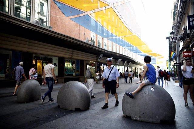 Turistas y vecinos de la zona Centro de Madrid pasean por la calle Preciados bajo la sombra gracias a los toldos instalados.