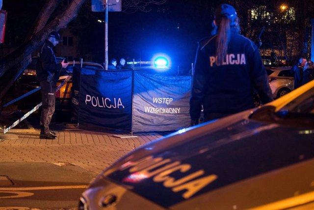 Agentes de Policía de Polonia junto con su coche asistiendo a un incidente