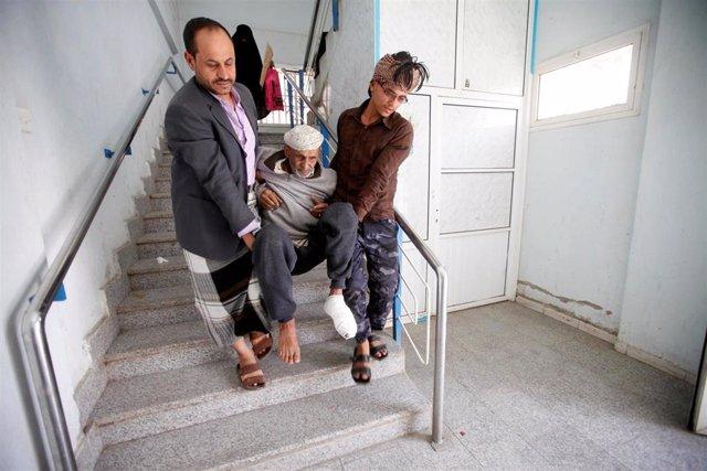 Personas cargando a un enfermo en Saná, Yemen