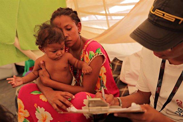 Mujer venezolana con su bebé en Colombia