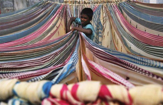 Un niño trabaja en una fábrica de telas