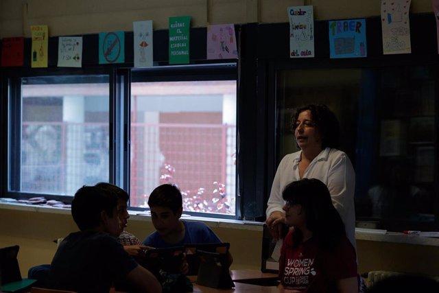 Una profesora imparte una clase en el aula de un colegio.