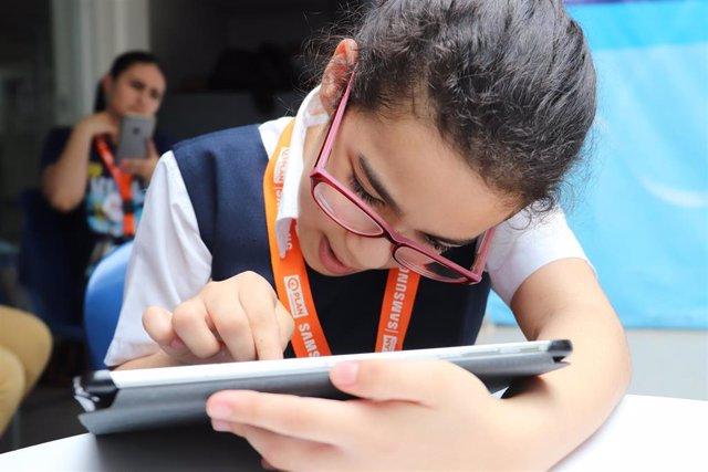 Una niña mira una tablet