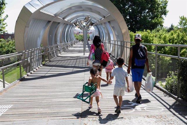 Una familia (una pareja con tres niños) se dirige a cruzar el túnel de Madrid Río para refrescarse de las altas temperaturas